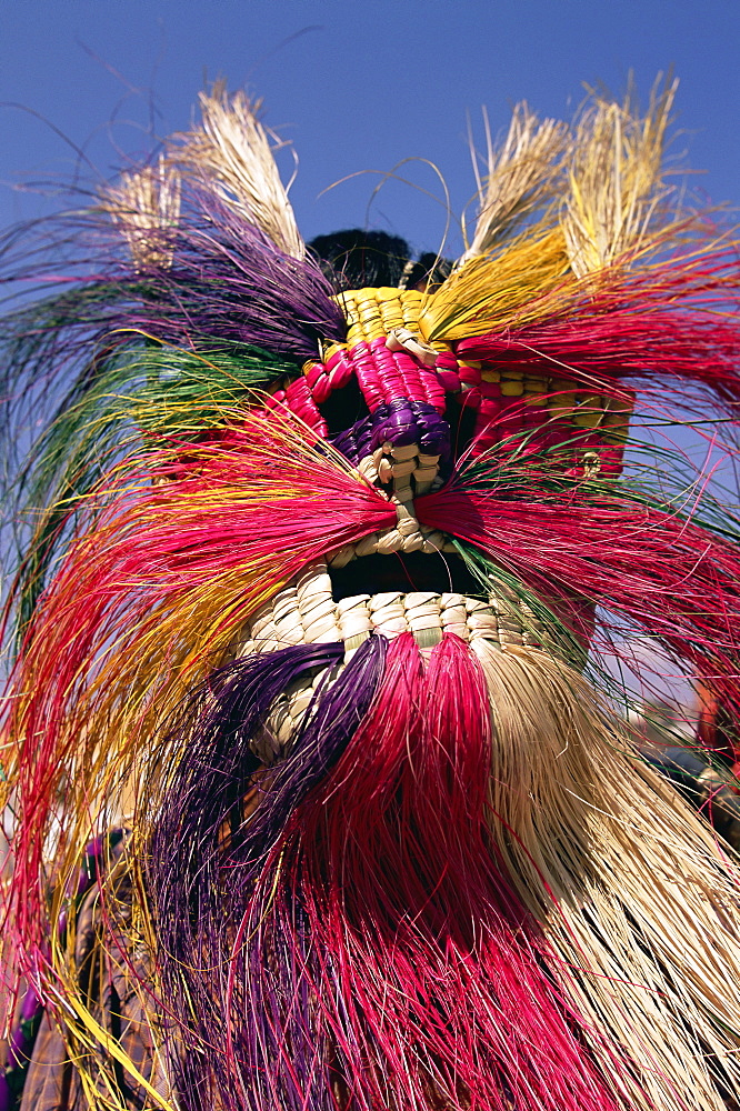 Head and shoulders portrait of a person wearing a brightly coloured straw mask, Oaxaca, Mexico, North America