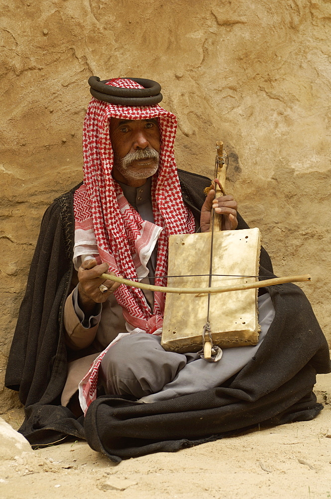 Bedouin man in traditional dress playing a musical instrument, Beida (Little Petra), Jordan, Middle East