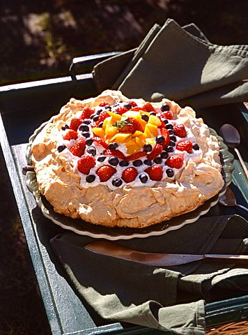 Meringue pie with strawberries, bilberries and cream, Italy