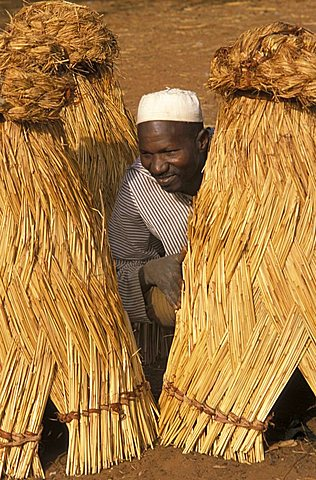 Local man among heaps of straw,  Republic of Niger, West Africa, Africa