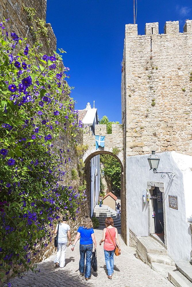 Tourists walk in the alleys close to the old castle in the fortified town of Obidos, Oeste, District of Leiria, Portugal, Europe