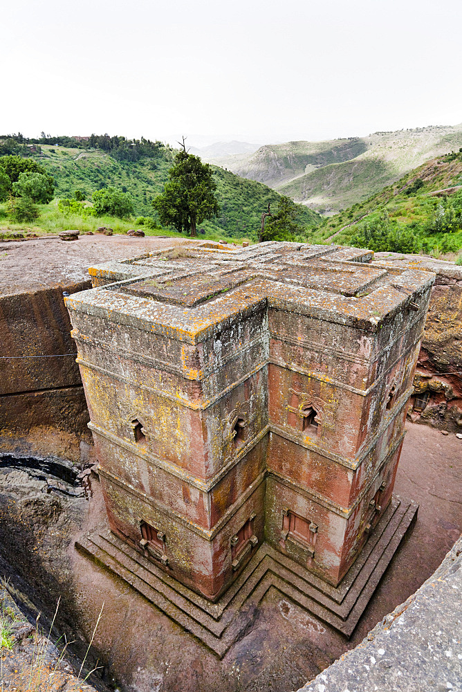 The rock-hewn churches of Lalibela in Ethiopia. Pilgrim praying in front of a church.  The churches of Lalibela have been constructed in the 12th or 13th century. They have been hewn from the solid rock and are considered to be one of the largest monolithic structures ever build by mankind, Africa, East Africa, Ethiopia, Lalibela