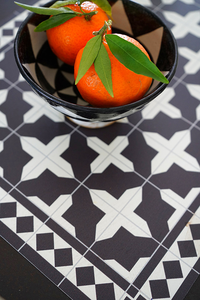 Tangerine in a bowl on squared background, Italy, Europe