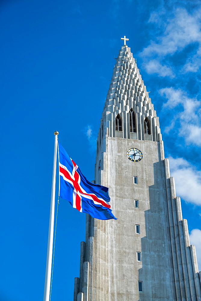 Hallgrimskirkja. Cathedral of Reykjavik with waving Iceland flag on a beautiful day.
