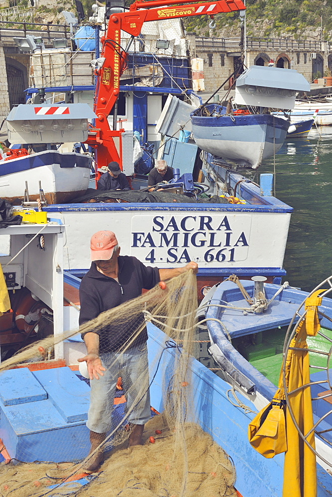 A fisherman gathers the nets after being at sea in the port of Cetara, Amalfi Coast, Campania, Italy. Behind him, a boat with a very typical name: Holy Family.
