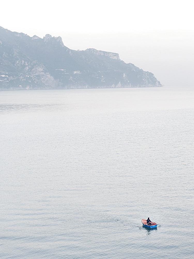 A lonely fisherman paddles on his small boat off the coast of Atrani, Amalfi Coast, Campania, Italy, Europe