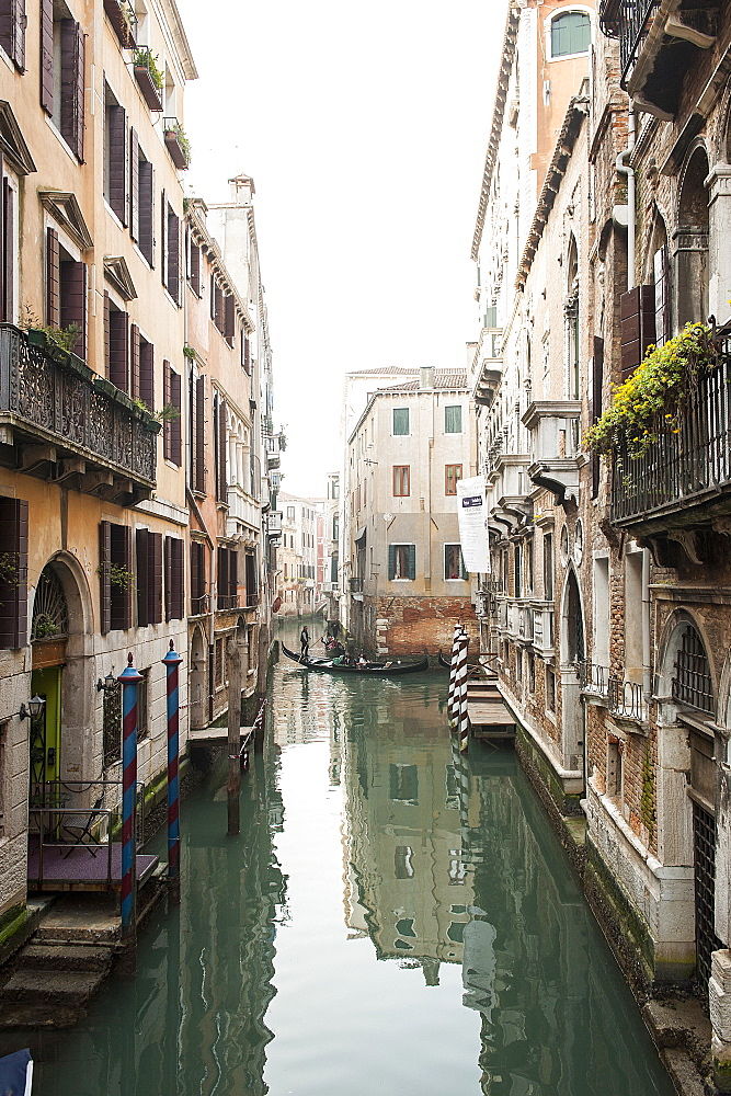 A view over the canal in winter time, in the distance you can see a gondola, a typical boat used in Venice to wade channels led by a sailor, Veneto, Italy, Europe