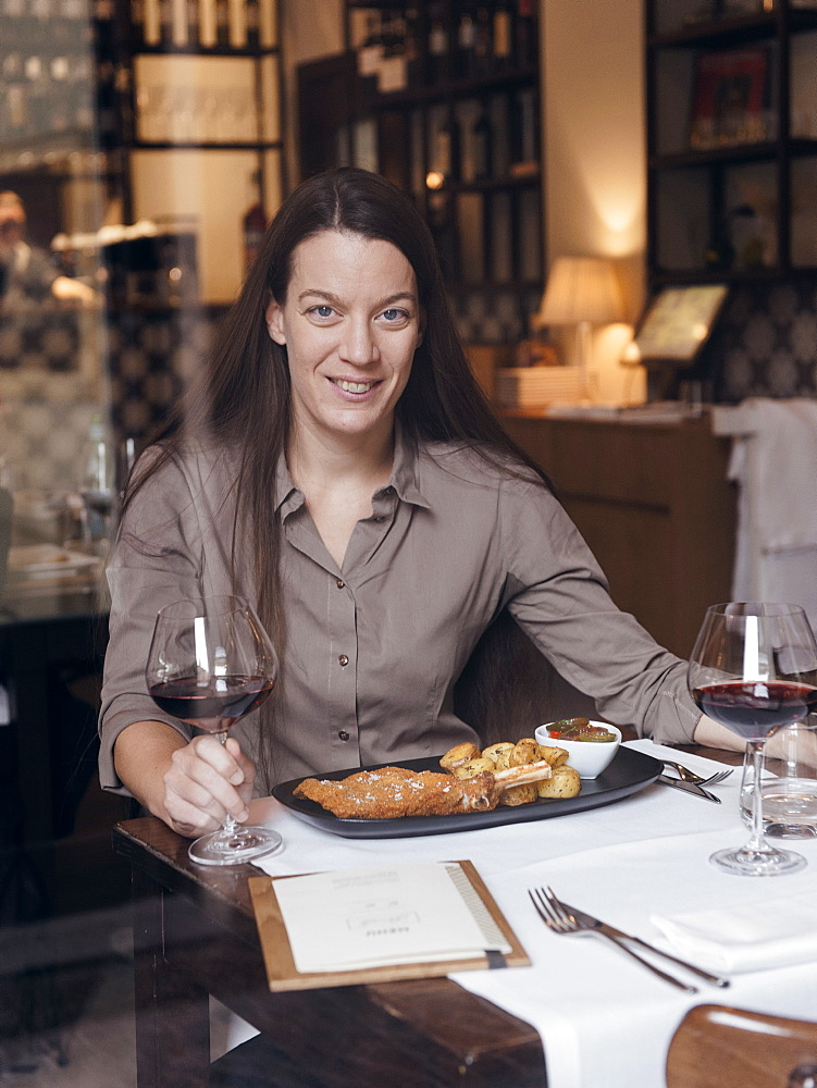 Portrait of the owner of the Restaurant Brunello in Milano along with one of their traditional dishes: Cotoletta Milanese served with baked french potatoes and a tomatoes salad with a glass of red wine
