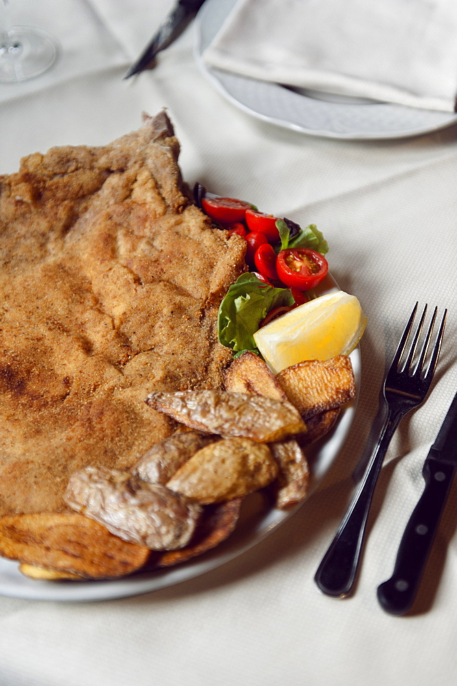 Cotoletta Milanese cooked by Restaurant Damm atra in Milano served with fried potatoes skind and tomatoes salad, Milan, Italy, Europe