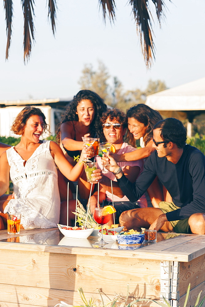 Girls and boys at sunset toast with an aperitif, EcoVillage Maremirtilli, Capaccio Paestum, Campania, Italy, Europe