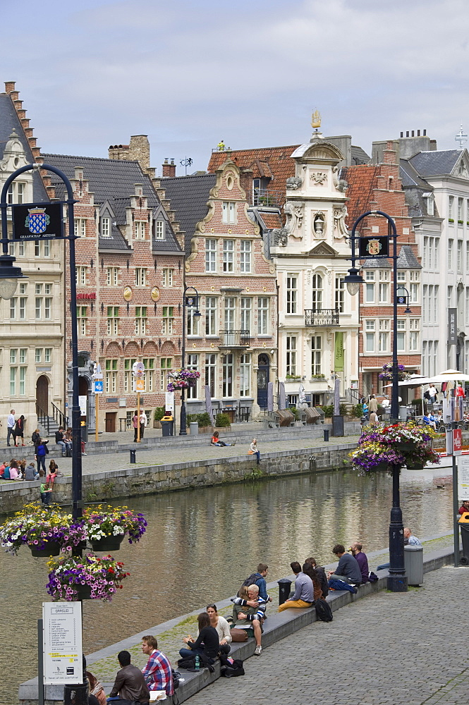 Students relaxing along the banks of the Graslei, Baroque style Flemish gables in the background, Ghent, Belgium, Europe