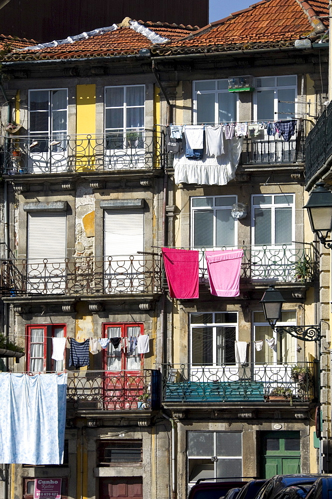 Flats in a residential street with traditional wrought iron balconies, washing hanging out in the sunshine, Oporto, Portugal, Europe