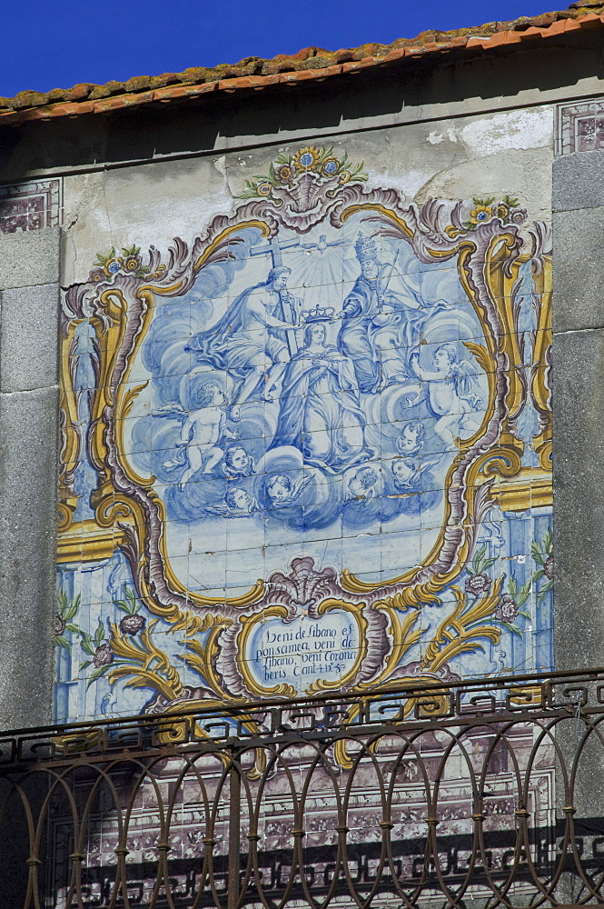 A beautiful blue and white tiled azuleju tableau with elaborate gold tiled frame preserved in an old wall in the City of Oporto, Portugal, Europe