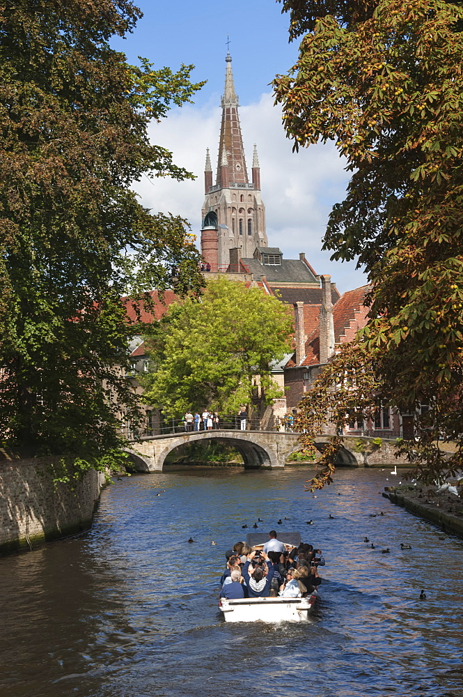 Bridge to Begijnhof, and spire of Church of Our Lady, tourist launch, Bruges, UNESCO World Heritage Site, Belgium, Europe