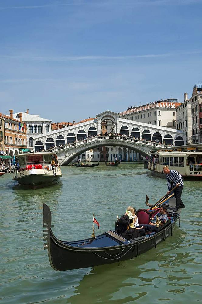 Water bus and gondola on the Grand Canal with the Rialto Bridge in the background, Venice, UNESCO World Heritage Site, Veneto, Italy, Europe
