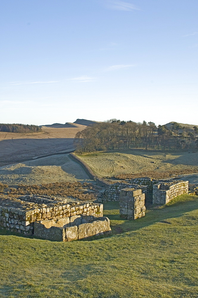 North gateway to Housesteads Roman Fort, stone water storage tank in foreground, looking east to Sewingshields Crag, Hadrians Wall, UNESCO World Heritage Site, Northumbria, England, United Kingdom, Europe