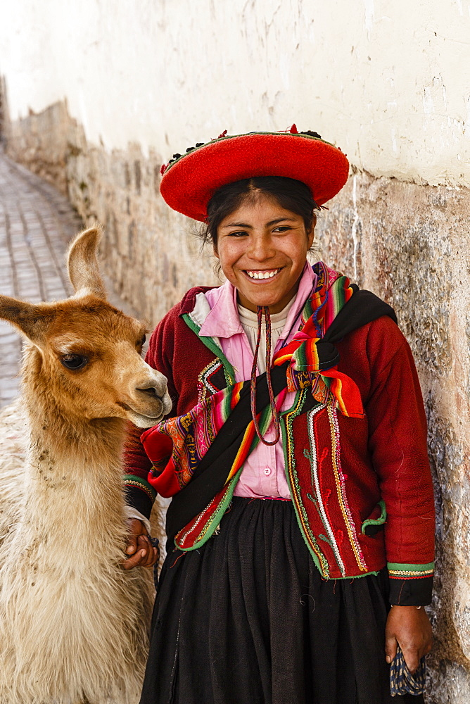 Portrait of a Quechua girl in traditional dress with a llama, Cuzco, Peru, South America