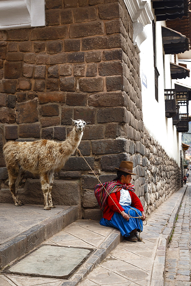 Quechua woman with llama along an Inca wall in San Blas neighborhood, Cuzco, Peru, South America