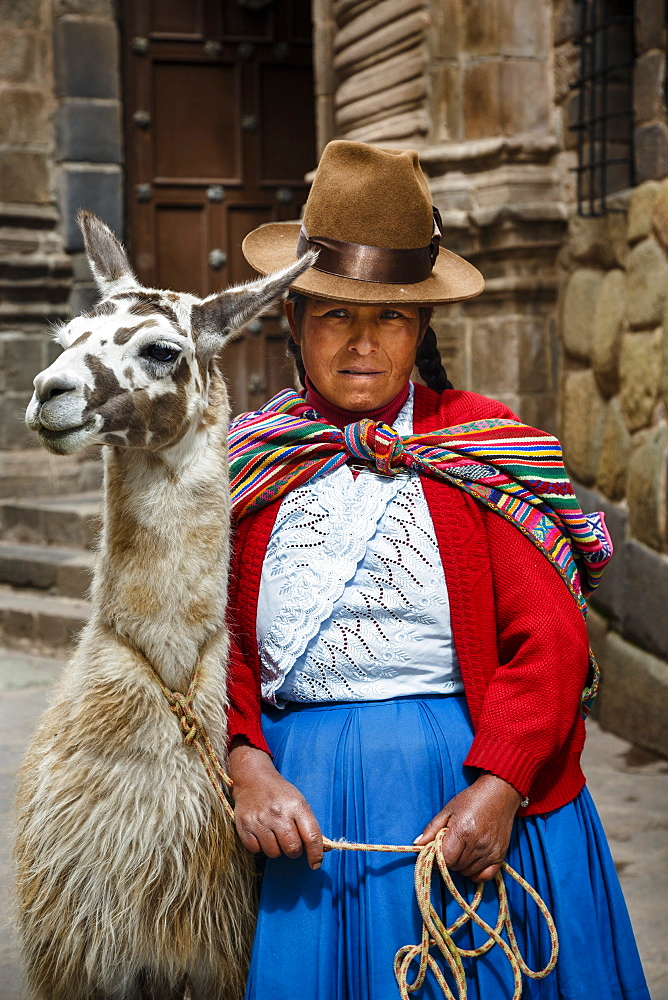 Portrait of a Quechua woman with llama along an Inca wall in San Blas neighborhood, Cuzco, Peru, South America