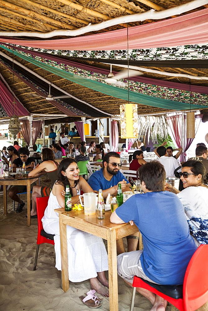 People sitting at La Plage restaurant in Ashvem, Goa, India, Asia