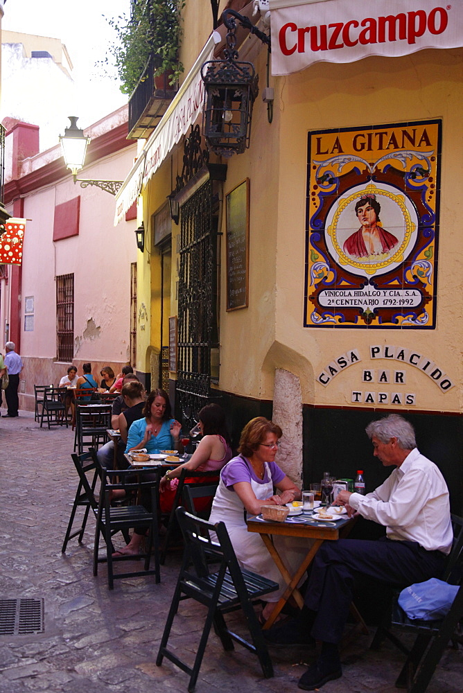 People sitting at a tapas bar in Barrio Santa Cruz, Seville, Andalucia, Spain, Europe