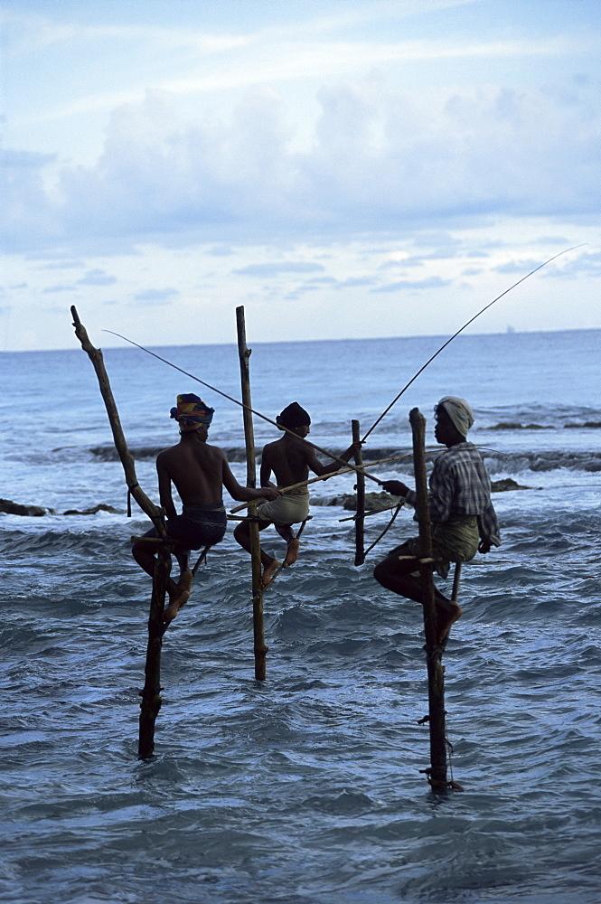 Stilt fishermen fishing from their poles between Unawatuna and Weligama, Sri Lanka, Indian Ocean, Asia