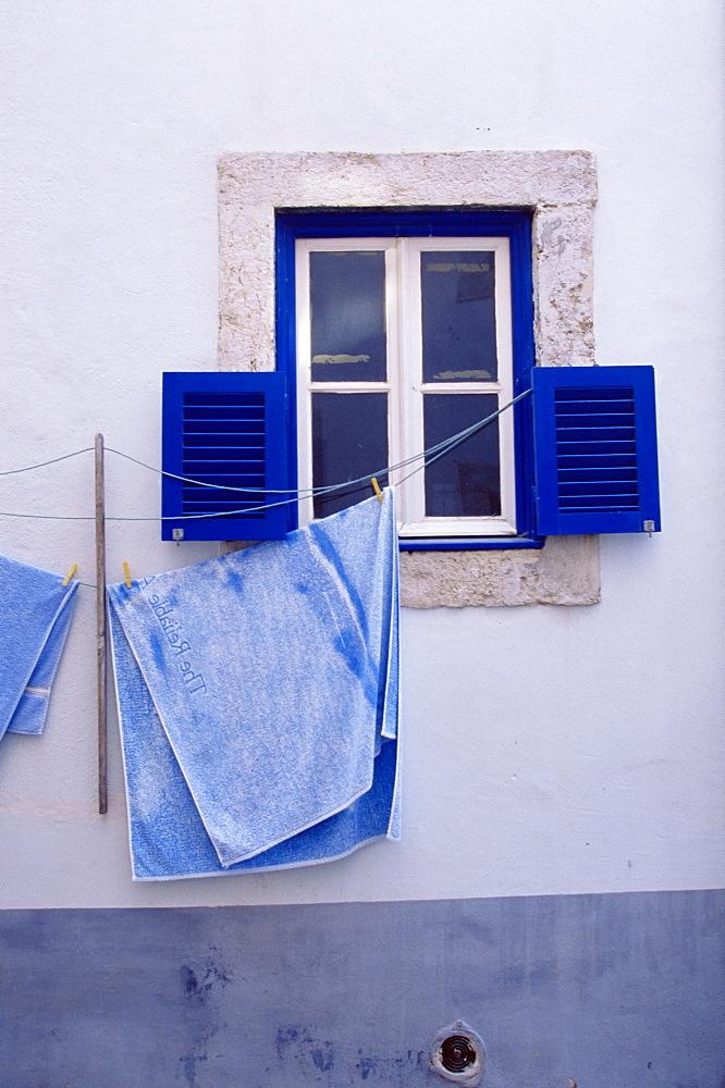 Laundry hanging on line at window in the Moorish quarter of Alfama, Lisbon, Portugal, Europe