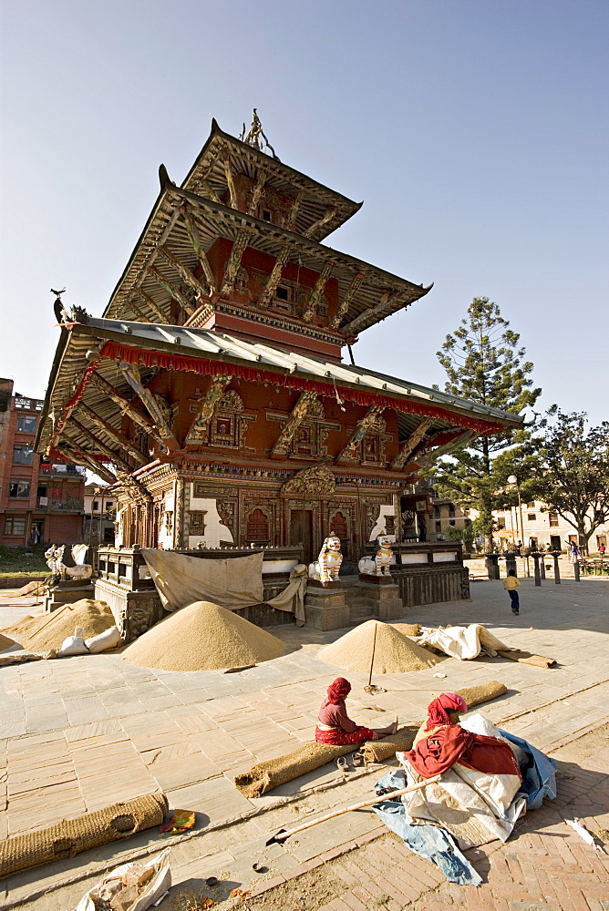 Piles of grain in front of the triple roofed pagoda of the Rato Machendranath temple, Patan, Kathmandu, Nepal, Asia