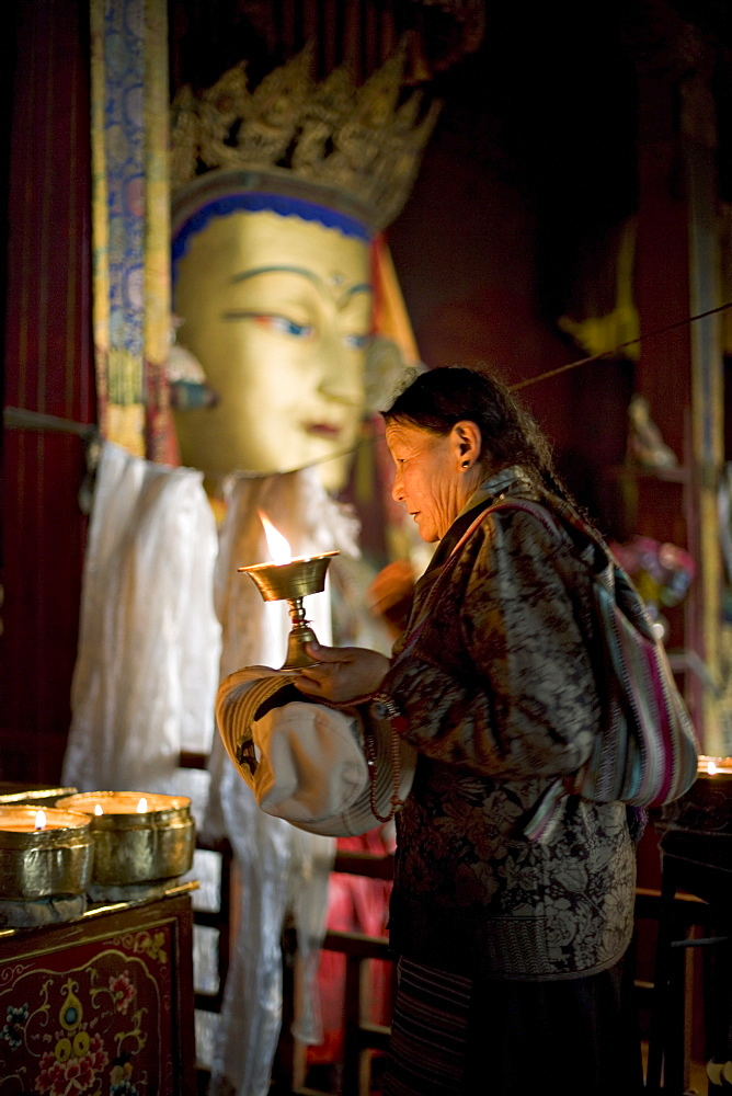 Woman adding yak butter from her butter lamp to those in the Buddhist temple, Meru Nyingba monastery, Bharkor, Lhasa, Tibet, China, Asia