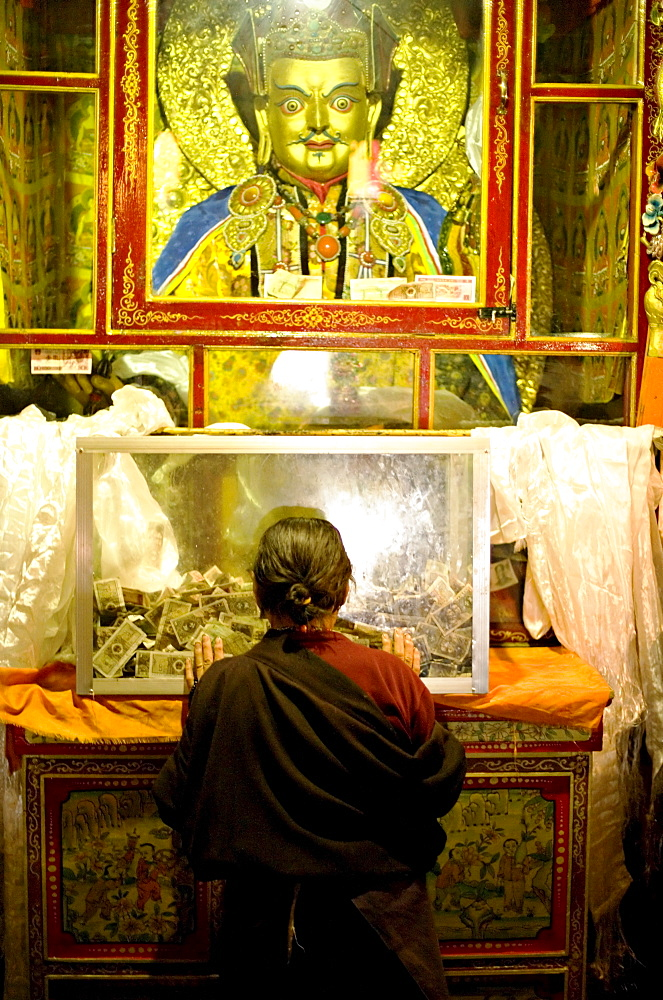Woman pays respect at Meru Nyingba Buddhist monastery, Bharkor, Lhasa, Tibet, China, Asia