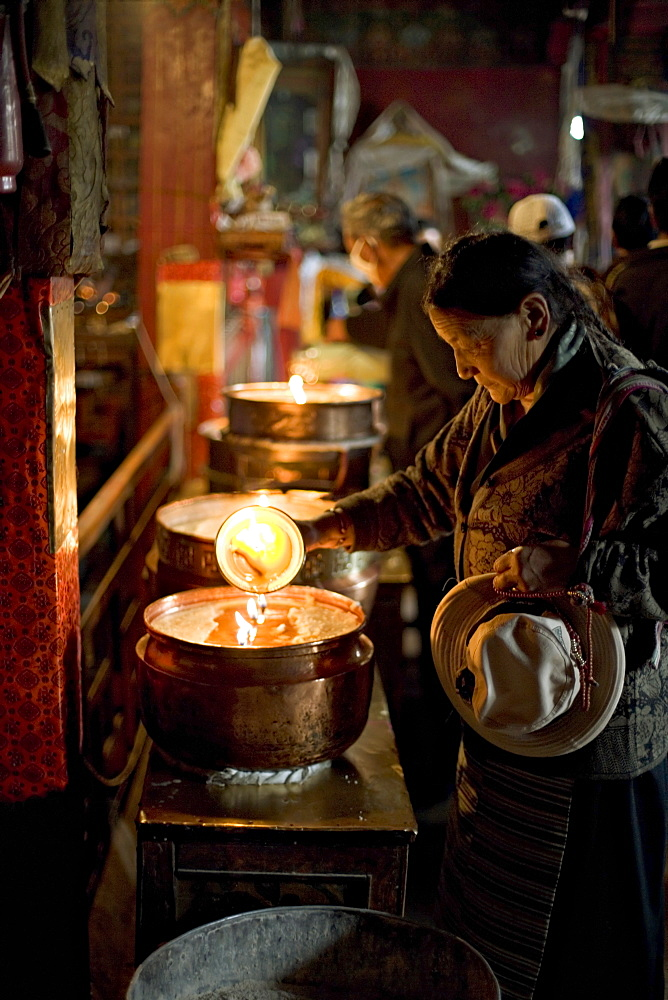 Woman adding the melting yak butter from her lamp to those of the temple, Meru Nyingba monastery, Bharkor, Lhasa, Tibet, China, Asia