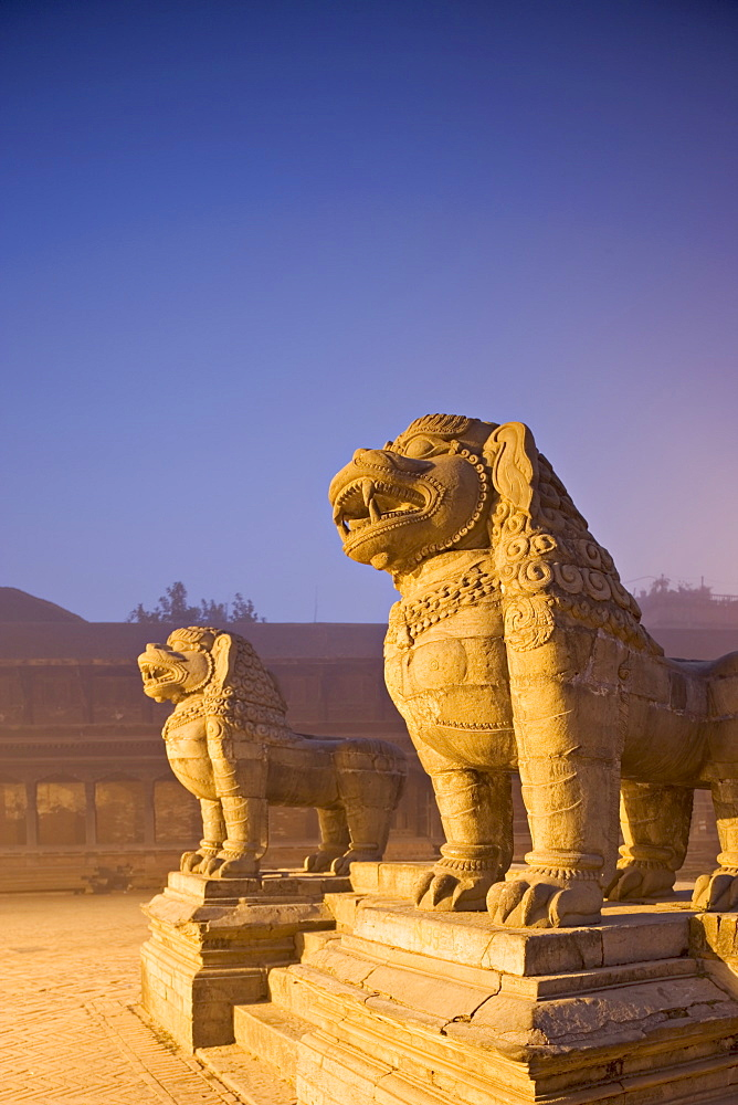 Stone lions, Durbar Square, Bhaktapur, Kathmandu valley, Nepal. Foggy winter dawn, november 2005.