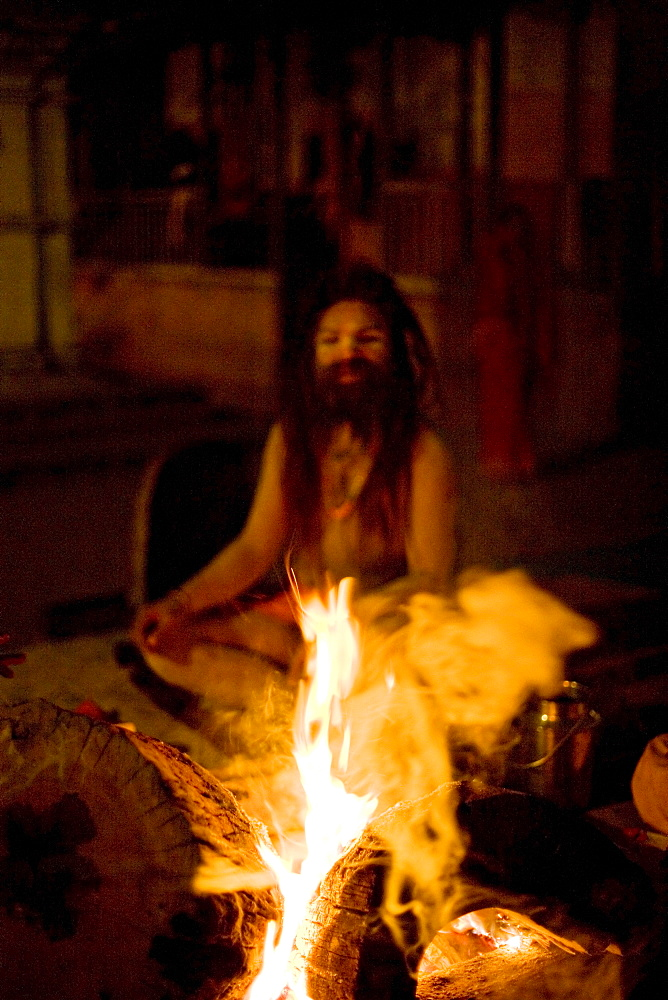 Holy man (sadhu) wearing dreadlocks and covered in ash, beside a fire, during the Hindu festival of Shivaratri, Pashupatinath, Kathmandu, Nepall, Asia