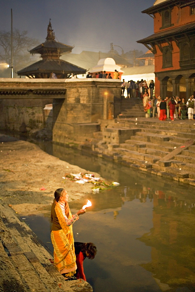 Two women making offerings (puja) before dawn by the Bagmati river, outside the Shiva temple during the Hindu festival of Shivaratri, Pashupatinath, Kathmandu, Nepal, Asia