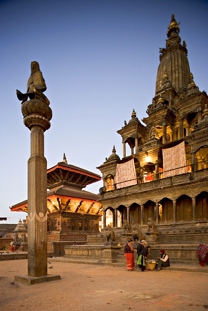Durbar Square at dawn with Garuda statue on column facing Krishna Mandir temple built in 1637 in Indian style, with twin roofed pagoda style Jagannarayan temple behind, Patan, Kathmandu Valley, UNESCO World Heritage Site, Nepal, Asia