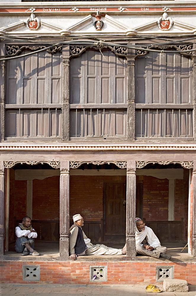 Three old men watch the world go by on a street in Bhaktapur, Kathmandu valley, Nepal, Asia