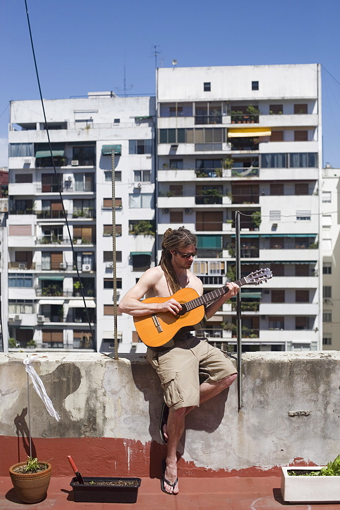 Man playing guitar on rooftop, Buenos Aires, Argentina, South America