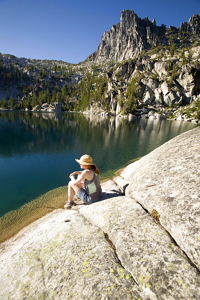 Woman sitting on the shore of Lake Viviane, Prusik Peak, Enchantment lakes, Alpine Lakes Wilderness, Levenworth, Washington State, United States of America, North America - 757-203