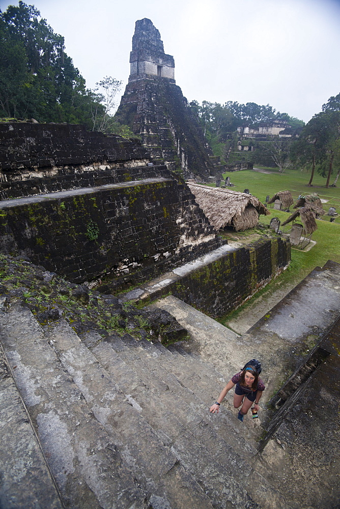 Woman climbing stairs at Mayan archaeological site, Tikal, UNESCO World Heritage Site, Guatemala, Central America