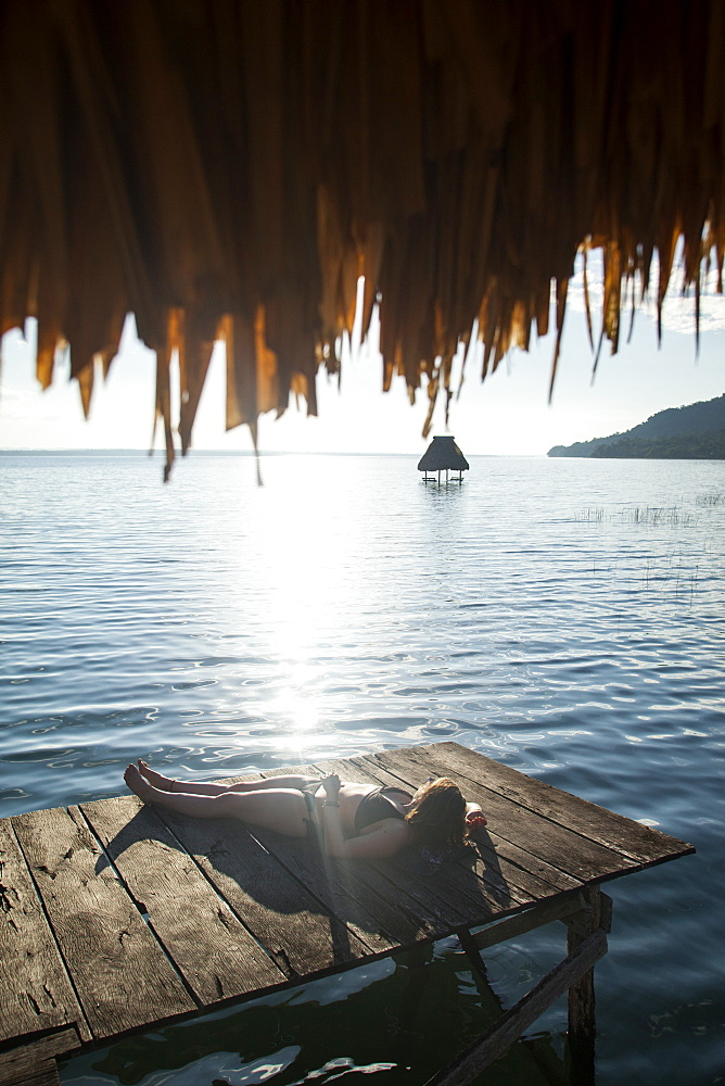 Woman relaxing on dock, El Remate, Lago Peten Itza, Guatemala, Central America