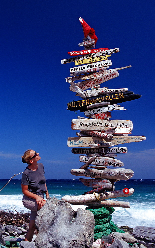 Tourist and Signpost on the beach, Netherlands Antilles, Bonaire, Caribbean Sea