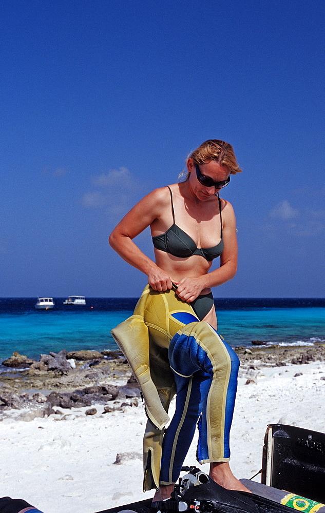 Woman preparing to dive on the beach, Netherlands Antilles, Bonaire, Caribbean Sea