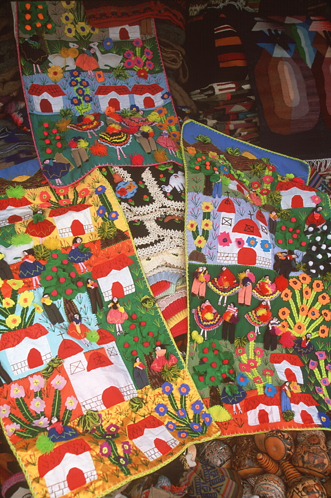 Appliqued village scenes are examples of the varied folkart to be found in the handicraft market in Miraflores, Lima, Peru