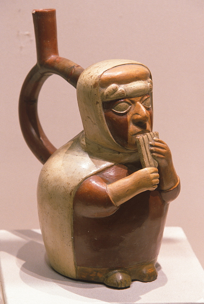 Mochica (Moche) Culture, 200BC-800AD, north coast ceramic 'stirrup-spout' vessel with a musician blowing a panpipe, Peru