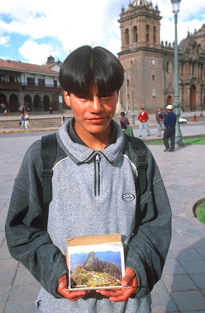Ancient capital of the Incas the Plaza de Armas with a young boy selling postcards, Cuzco, Highlands, Peru