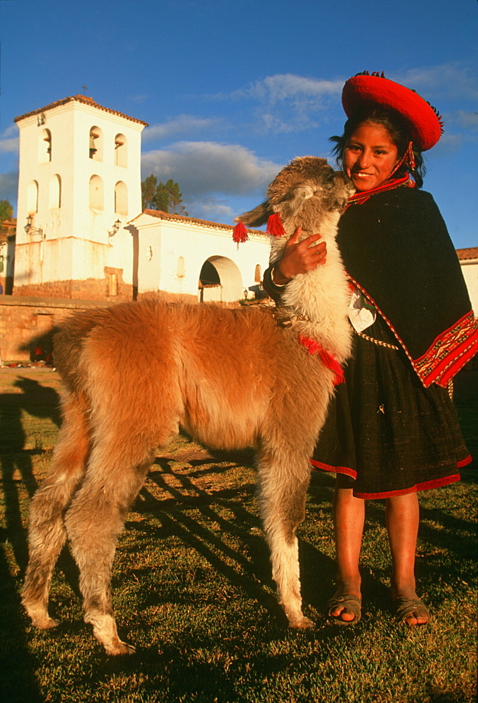 Chincheros an ancient village near Cuzco its colonial church is built on Inca foundations young Indian girl and pet llama in main plaza, Highlands, Peru