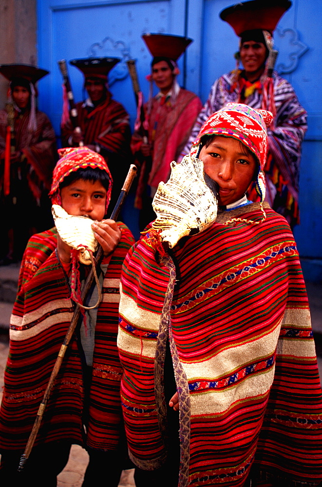 Pisac, village in Sacred Valley near Cuzco and one of world's most colorful markets village elders and boys blowing shell horns, Highlands, Peru
