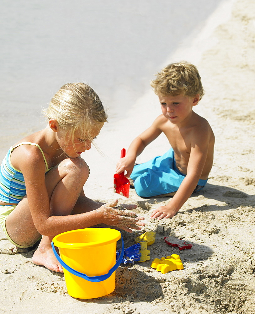 Boy and girl (6-8) on beach making sandcastles