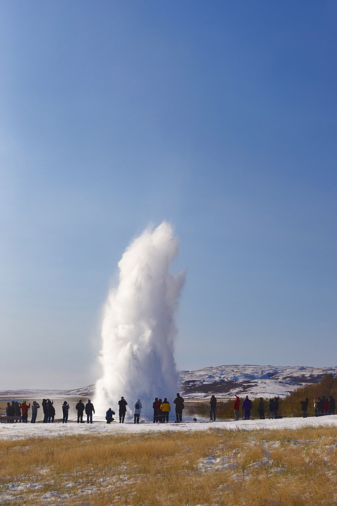 Tourists watching geyser erupting, Strokkur (the Churn) erupts every 5-10 minutes to heights of up to 20 meters (70ft), Geysir, Golden Circle, Iceland, Polar Regions