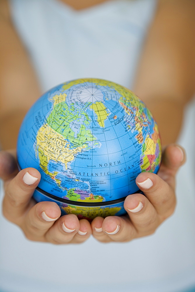 Woman's hands holding world globe